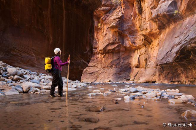 """Turista percorre a trilha """"The Narrows"""", que segue o curso do rio entre paredões rochosos"""